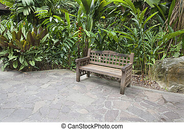 Wood Bench in Tropical Garden with Stone Paver Patio