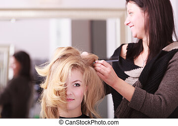 Beautiful smiling girl with blond wavy hair by hairdresser...