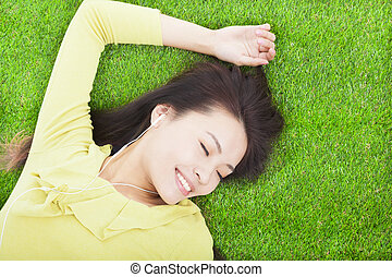 High angle view of a young woman listening music on grass