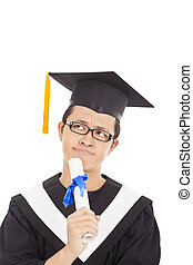 Thoughtful graduation man wearing a mortarboard and looking...