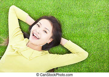 happy  woman holding head and lying on a meadow