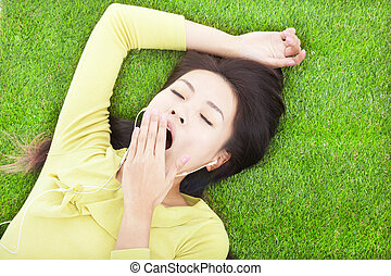 smiling woman yawning and lying on grass - smiling woman...