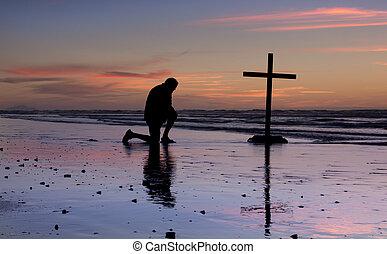 Sunset Beach Prayer Cross - Man kneel at a cross on a beach...