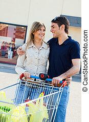 shopping cart - portrait of young couple pushing shopping...