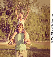Family Father Man and Son Boy sitting on shoulders Outdoor Happiness emotions Lifestyle with summer nature on background