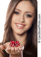 winning combination - smiling girl holding a pair of dice...