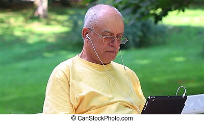 Senior man using digital tablet - Senior man enjoying music...