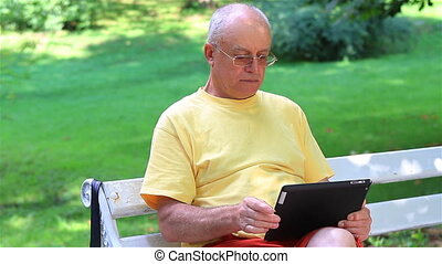 Senior man using digital tablet in summer park
