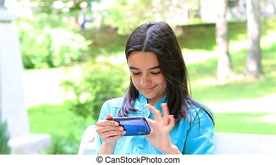Teenage girl playing on smart phone in summer park