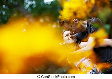 Happy girl in the arms of her boyfriend among flowers -...
