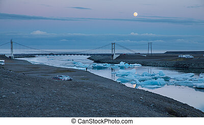 blue icebergs floating and full moon
