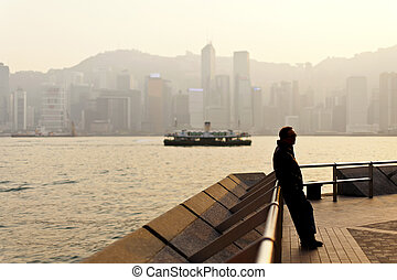 Man standing along Victoria Harbor