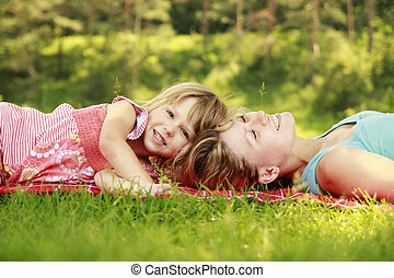 Mama and her little daughter playing on grass - a Mama and...