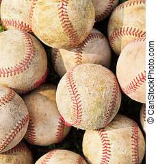 closeup of pile up a stack of old baseball in green