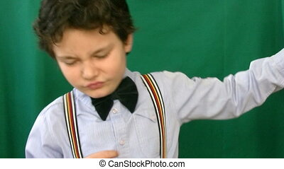 Child dancing in front of a green screen