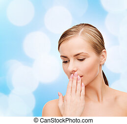 young woman doing hush gesrute - health and beauty concept -...