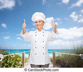 smiling female chef showing thumbs up - cooking, gesture and...