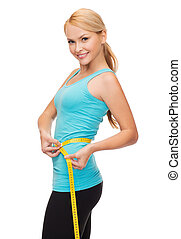 sporty woman with measuring tape - diet, sport and heath...