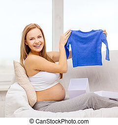 smiling pregnant woman opening gift box - pregnancy,...