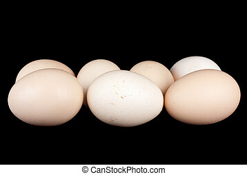 Few chicken eggs over the black background
