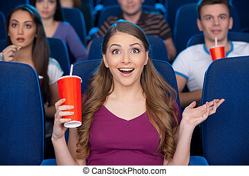 What an exciting movie Beautiful young woman holding cup...