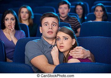 Watching horror movie. Shocked young couple bonding to each other while watching movie at the cinema