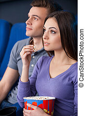 What an exciting movie! Excited young couple eating popcorn while watching movie at the cinema