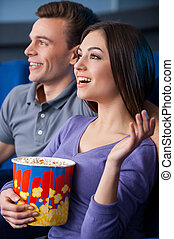 What an exciting movie! Side view of happy young couple eating popcorn while watching movie at the cinema