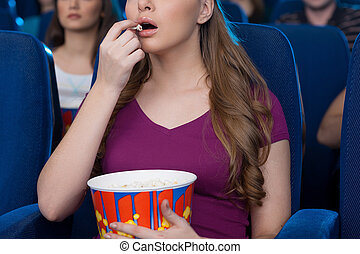 Eating popcorn at the cinema Cropped image of beautiful...