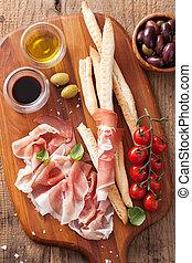 italian prosciutto ham grissini bread sticks tomato olive...