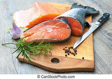 Raw salmon fish steaks with fresh herbs on cutting board