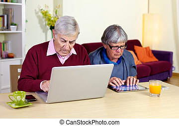 Senior couple in love with technology tablet and computer -...