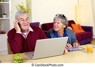 Happy grandfather talking on the phone with son at home