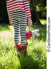 Stripy legs and teddy in meadow.