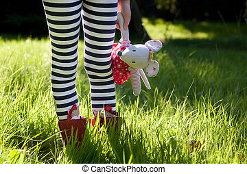 Stripy legs and teddy in a meadow.