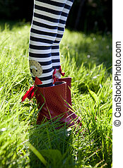 Stripy legs and red boots on grass.