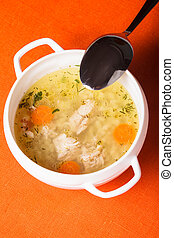 Chicken broth - A chicken broth in white ware on the orange...