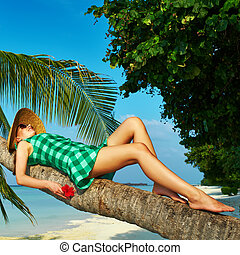 Woman lying down on a palm tree at tropical beach - Woman in...