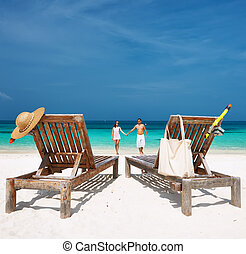 Couple in white running on a beach at Maldives - Couple in...