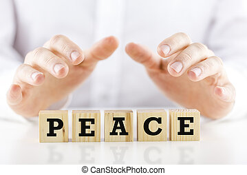 Man holding protective hands above the word Peace - Man...