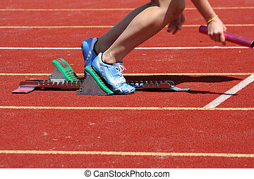 Runner leaving starting blocks with baton