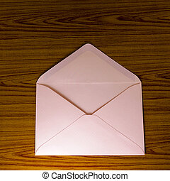 soft pink envelope on wooden background