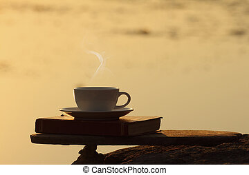 Afternoon coffee cup and book on wooden board with golden...