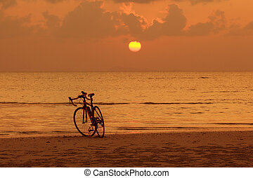 Silhouette of a bike on the beach at golden sunset background