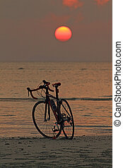 Silhouette of a bike on the beach at red sunset background