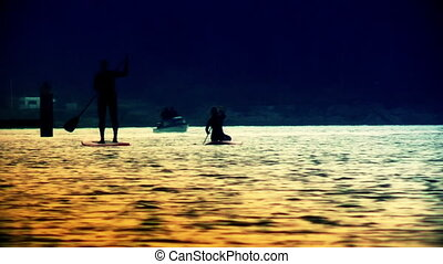 Silhouettes paddling on river - Silhouettes paddling on a...