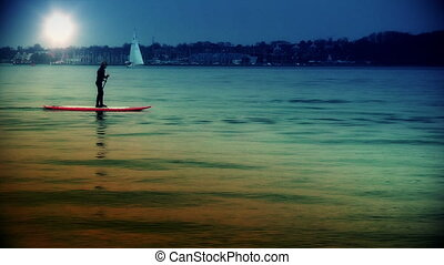 Silhouette paddling at sunset