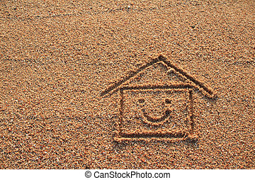 Happy house and smile icon drawn on beach sand