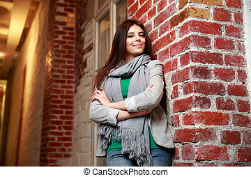 Portrait of a young smiling woman with arms folded leaning on the brick wall