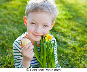 easter time - cute smiling little boy holding yellow bright...